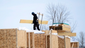A worker carries wood as a house under construction is shown in a new subdivision in Beckwith, Ont., on Wednesday, Jan. 11, 2018. (THE CANADIAN PRESS / Sean Kilpatrick)