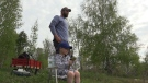 Kevin Koning stands behind his son Bryce, 4, while fishing at Lake Margaret in St. Thomas, Ont. on Sunday, May 16, 2021 (Brent Lale / CTV News)