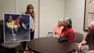 Dr. Marisa Azad shows off her painting to a family. (Photo courtesy: Dr. Marisa Azad)