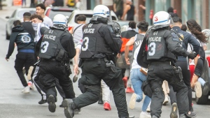 Pro-Palestinian supporters run from police following a demonstration in Montreal, Sunday, May 16, 2021. THE CANADIAN PRESS/Graham Hughes