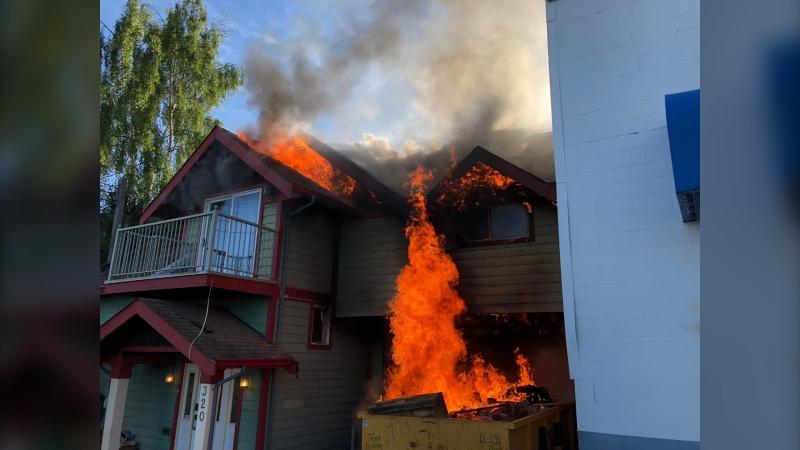 A photo shared on the Victoria firefighters union's Twitter account shows flames coming from both the dumpster and the roof of the building. (Twitter/VictoriaFire730)