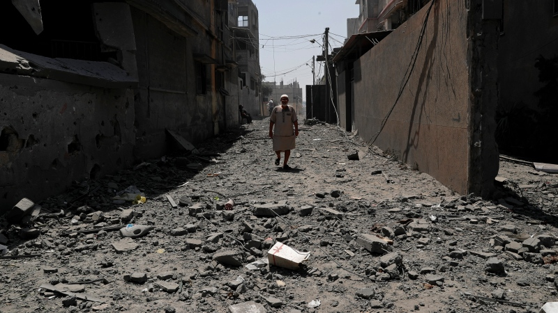 A man walks amid the rubble from buildings that were hit in Israeli airstrikes, on a street in Gaza City, Sunday, May 16, 2021. (AP Photo/Adel Hana)