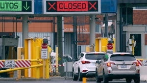"Vehicles wait in line to cross into Canada at the Peace Bridge Plaza, Wednesday, March 18, 2020, in Buffalo N.Y. The Canada-U.S. border will be closed to non-essential traffic in both directions ""by mutual consent,"" President Donald Trump confirmed Wednesday, as efforts across the continent to contain the widening COVID-19 pandemic continued to upend daily life in North America. (AP Photo/Jeffrey T. Barnes)"