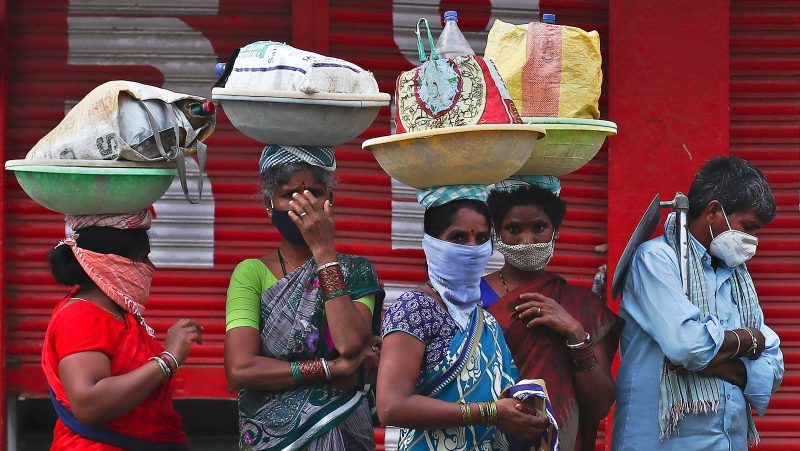 Daily wage laborers wearing protective face masks wait at a pavement for transportation during a lockdown imposed to curb the spread of the coronavirus in Hyderabad, India, Sunday, May 16, 2021. (AP Photo/Mahesh Kumar A.)