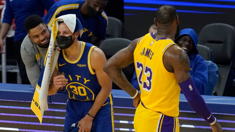 Los Angeles Lakers forward LeBron James (23) watches as Golden State Warriors' Kent Bazemore, from left, Stephen Curry (30) and Draymond Green laugh during the first half of an NBA basketball game in San Francisco, Monday, March 15, 2021. (AP Photo/Jeff Chiu)