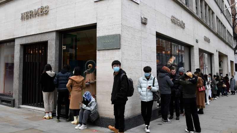 People line up outside a Hermes store in Mayfair in London, on April 12, 2021. (Alberto Pezzali / AP)