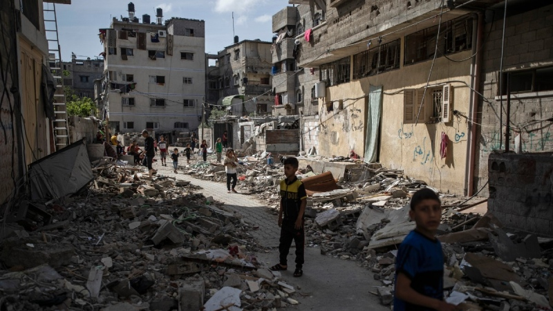 Palestinian children walk next to rubble from a house was that was hit by early morning Israeli airstrikes, in Gaza City, May 17, 2021. (Khalil Hamra / AP)