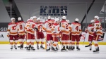 Calgary Flames players celebrate the team's overtime win against the Vancouver Canucks during an NHL hockey game in Vancouver, B.C., Sunday, May 16, 2021. THE CANADIAN PRESS/Darryl Dyck