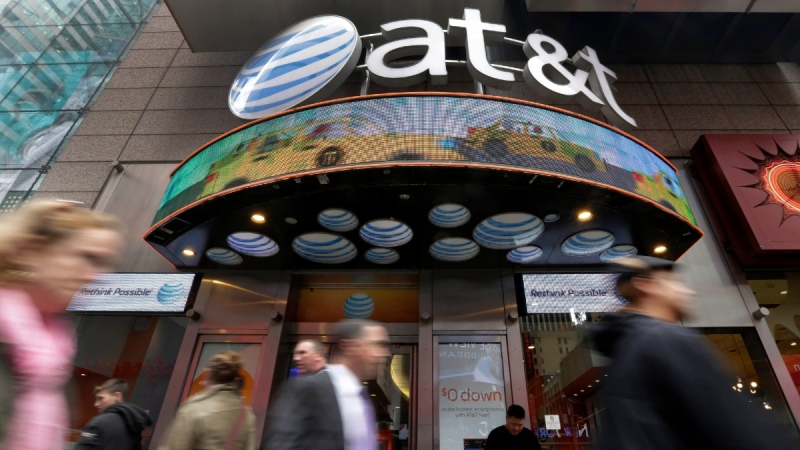 People pass an AT&T store in New York's Times Square, on Oct. 21, 2014.  (Richard Drew / AP)