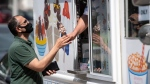 A person buys an ice cream cone at an ice cream truck at Commissioner's Park during the Canadian Tulip Festival in Ottawa, on Sunday, May 16, 2021. (Justin Tang/THE CANADIAN PRESS)