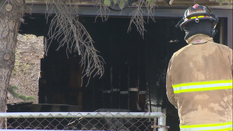A CFD member stands in front of a fire-damaged garage in Montgomery following a Monday morning fire.