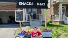 Jaxon Burne running his snack stand at the end of his driveway in Cambridge. (Credit: Morgan Wilson)