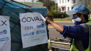 Airport workers spray the cargo of COVAX COVID-19 vaccines on arrival in Antananarivo, Madagascar, Saturday May 8, 2021. (AP Photo/Alexander Joe)