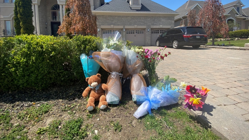 Flowers and a stuffed animal are left near the scene of crash that killed a 4-year-old boy on Athabasca Drive, near Dufferin Street in Vaughan. (Ken Enlow/CP24)