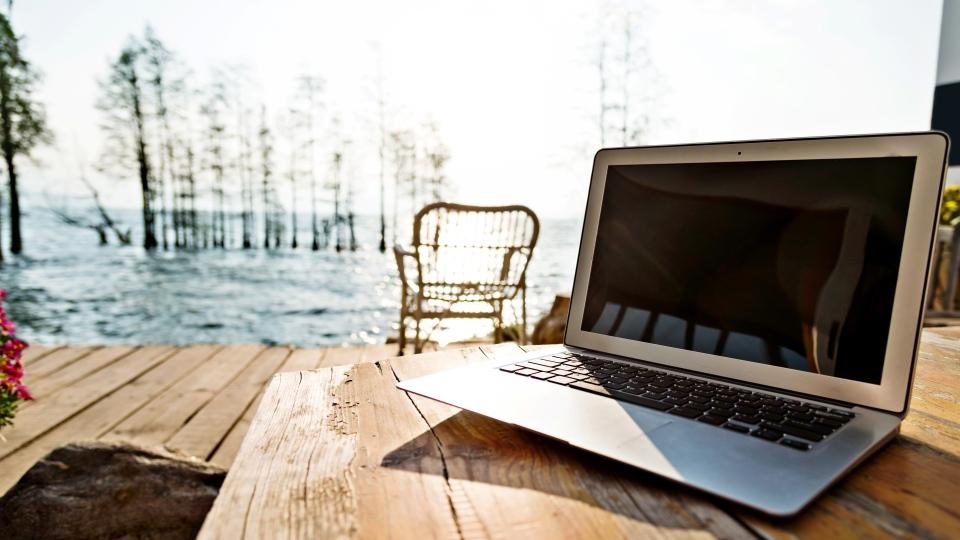 Laptop by a lake (iStock / baona)