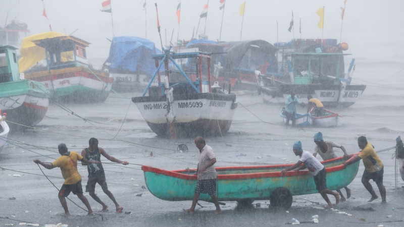 Fishermen try to move a fishing boat to a safer ground on the Arabian Sea coast in Mumbai, India, Monday, May 17, 2021. (AP Photo / Rafiq Maqbool)