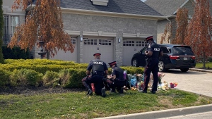 York Regional Police officers are seen laying flowers at the scene of a crash in Vaughan, Ont. where two young siblings were killed. (Ken Enlow/CP24)