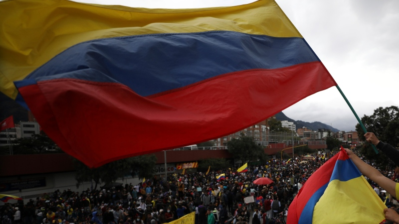A demonstrator waves a national flag during an anti-government protest in Bogota, Colombia, Saturday, May 15, 2021. (AP Photo/Fernando Vergara)