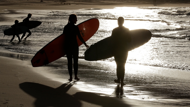 In this April 28, 2020, file photo, surfers walk along Bondi Beach in Sydney as coranavirus pandemic restrictions are eased. (AP Photo/Rick Rycroft, File)