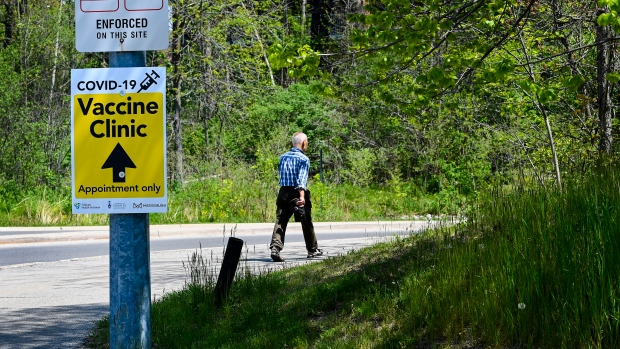 A man makes his way past signage to a mass COVID-19 vaccination centre at the University of Toronto's Mississauga campus during the COVID-19 pandemic in Mississauga, Ont., on Monday, May 17, 2021. THE CANADIAN PRESS/Nathan Denette