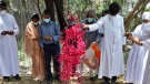 Indian Christian priests and others throw flower petals on the grave of Father Rolfie D'Souza's who died of COVID-19 after his burial at a cemetery in Prayagraj, India, Saturday, May 15, 2021. (AP Photo/Rajesh Kumar Singh)