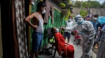 A heath worker in protective suit takes nasal swab sample of a woman to test for COVID-19 in a residential area in Gauhati, Assam state, India, Monday, May 17, 2021. (AP Photo/Anupam Nath)