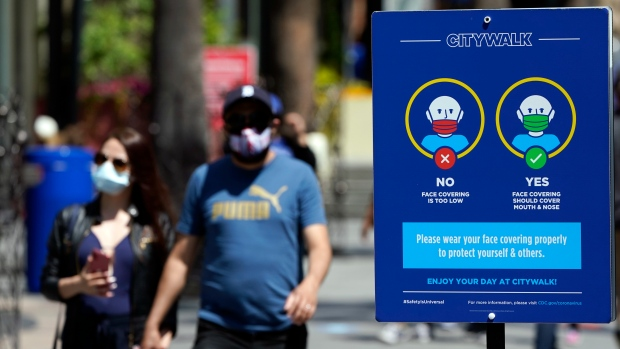 In this May 14, 2021, file photo, signs instruct visitors on the proper way to wear masks at the Universal City Walk in Universal City, Calif. California is keeping its rules for wearing facemasks in place until the state more broadly lifts its pandemic restrictions on June 15. (AP Photo/Marcio Jose Sanchez, File)