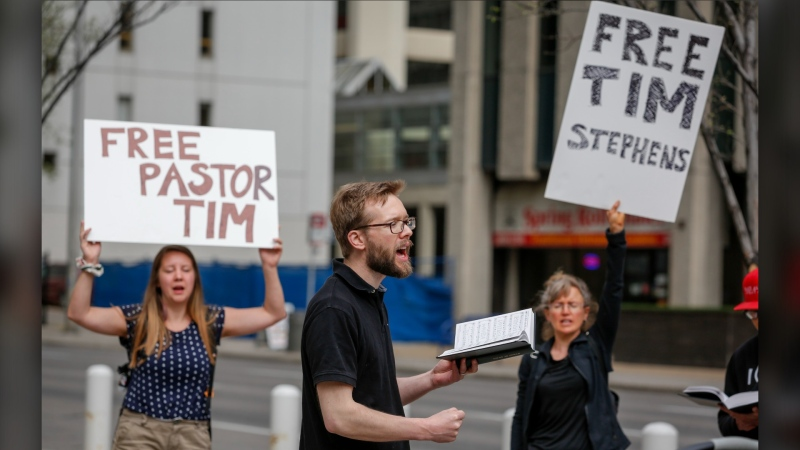 Supporters of Pastor Tim Stephens sing hymns and pray outside the Calgary Courts Centre in Calgary, Alta., Monday, May 17, 2021. (THE CANADIAN PRESS/Jeff McIntosh)