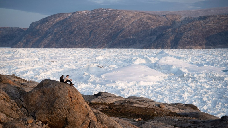 Student researchers sit on top of a rock overlooking the Helheim glacier in Greenland, on Aug. 16, 2019.  (Felipe Dana / AP)