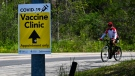 A person cycles past signage at a mass COVID-19 vaccination centre at the University of Toronto's Mississauga campus during the COVID-19 pandemic in Mississauga, Ont., on Monday, May 17, 2021. THE CANADIAN PRESS/Nathan Denette