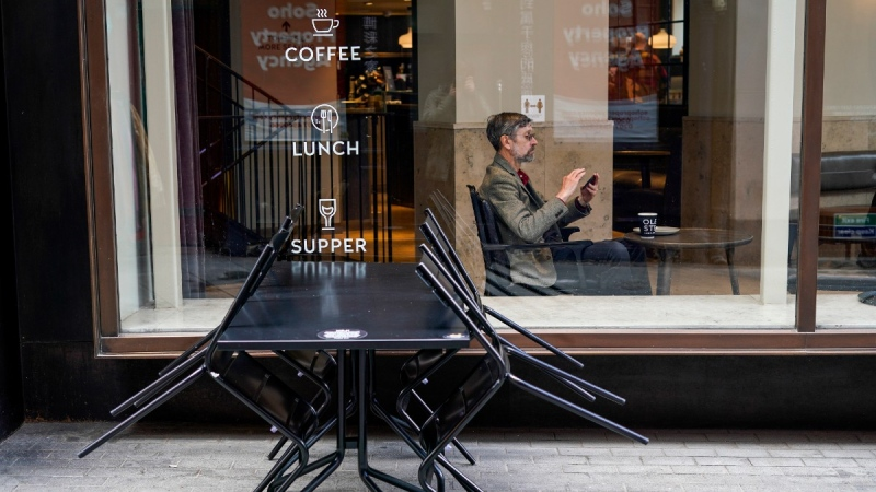 A man sits in a cafe in Soho, as pubs, cafes and restaurants in England reopen indoors under the latest easing of the coronavirus lockdown in London, on May 18, 2021. (Alberto Pezzali / AP)
