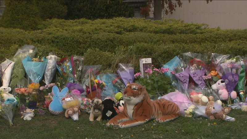 Flowers and stuffed animals are piled outside the Vaughan home where two young children were struck and killed in their driveway over the weekend.