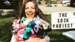 Jessica Baird poses with a pile of socks. The Sock Project gives pairs of funny and silly socks away for free to people suffering from chronic illnesses. (Photo courtesy of Jessica Baird/The Sock Project)