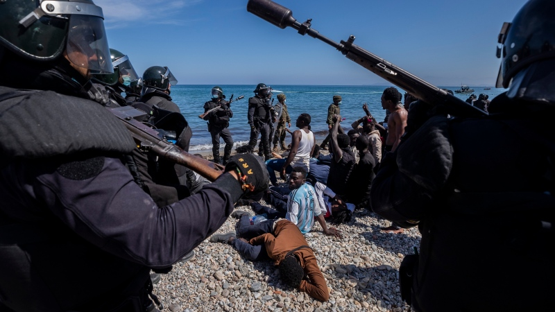Migrants are surrounded by Spanish police near the border of Morocco and Spain, at the Spanish enclave of Ceuta, on Tuesday, May 18, 2021.(AP Photo/Bernat Armangue)