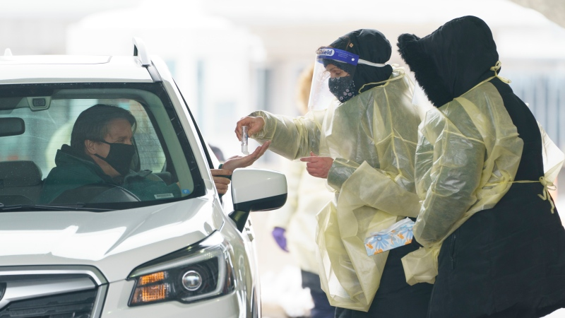A passenger is screened and gets a COVID-19 test while entering Canada from the United States at the land border crossing in Saint-Bernard-de-Lacolle, Que. on Monday, February 22, 2021. THE CANADIAN PRESS/Paul Chiasson