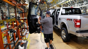 In this Sept. 27, 2018, file photo a United Auto Workers assemblyman installs the front doors on a 2018 Ford F-150 truck being assembled at the Ford Rouge assembly plant in Dearborn, Mich. (AP Photo/Carlos Osorio, File)