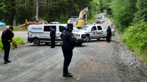 An excavator works in the background as police establish a checkpoint on McClure Main, a road that leads to the Cayacuse blockade camp, in the Cayacuse area on B.C.'s Vancouver Island, Monday, May 17, 2021. THE CANADIAN PRESS/Jen Osborne
