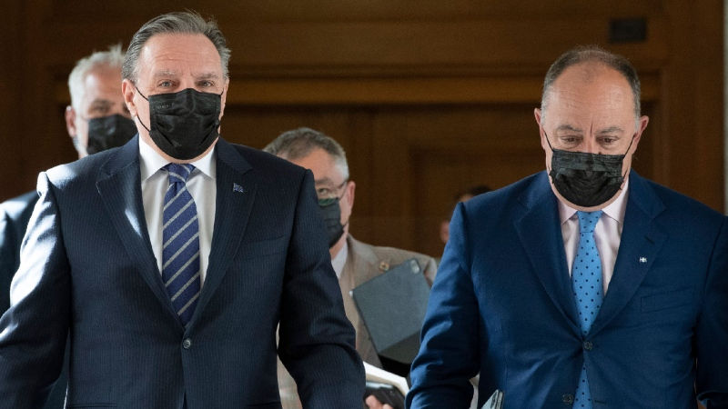 Quebec Premier Francois Legault, left, and Quebec Health Minister Christian Dube walk to a news conference on the COVID-19 pandemic, Tuesday, May 18, 2021 at the legislature in Quebec City. THE CANADIAN PRESS/Jacques Boissinot