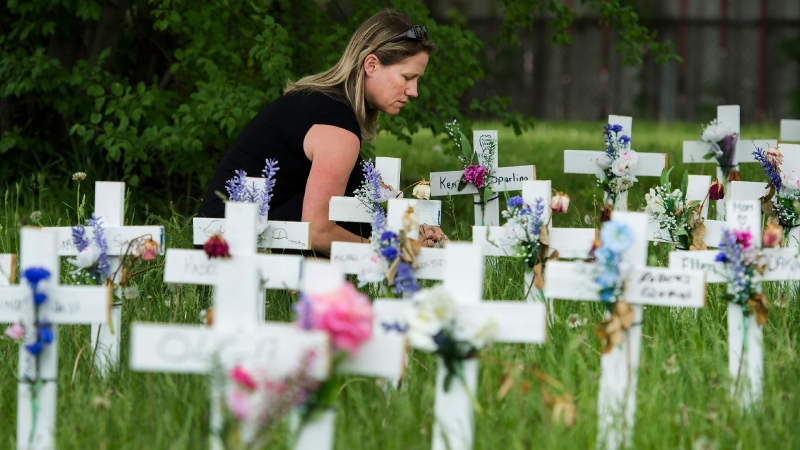 A women visits her father's cross along with others displayed outside the Camilla Care Community centre marking the deaths of multiple people that occurred during the COVID-19 pandemic in Mississauga, Ont., on Friday, May 29, 2020. THE CANADIAN PRESS/Nathan Denette