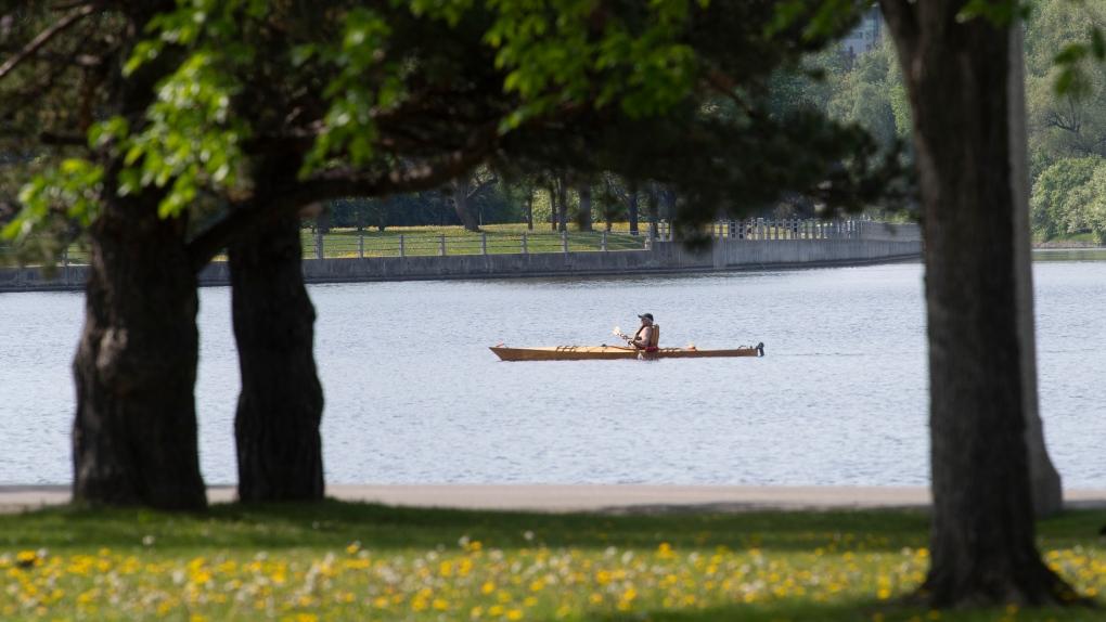 A man paddles across Dow's Lake