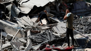 People inspect the rubble of destroyed residential building which was hit by Israeli airstrikes, in Gaza City, Thursday, May 20, 2021. (AP / Adel Hana)