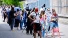 Families and youth aged 12 and older line up for a COVID-19 vaccine at Gordon A Brown Middle School in Toronto Wednesday May 19, 2021. THE CANADIAN PRESS/Nathan Denette