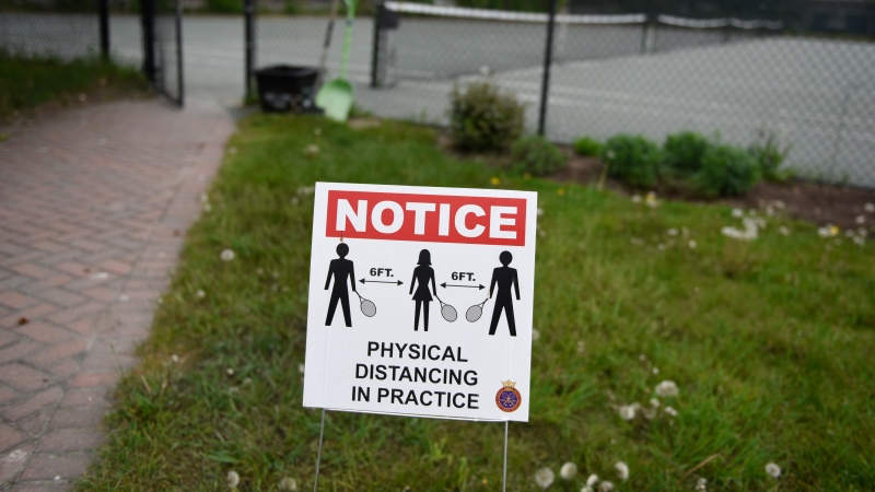 A physical distancing notice is seen at the Ottawa Tennis and Lawn Bowling Club in Ottawa, Friday, May 21, 2021, a day before tennis courts reopen as part of Ontario's phased reopening plan in the third wave of the COVID-19 pandemic. THE CANADIAN PRESS/Justin Tang