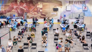 People are shown at the Bill Durnan Arena COVID-19 vaccination site in Montreal, Saturday, May 22, 2021. (THE CANADIAN PRESS / Graham Hughes)