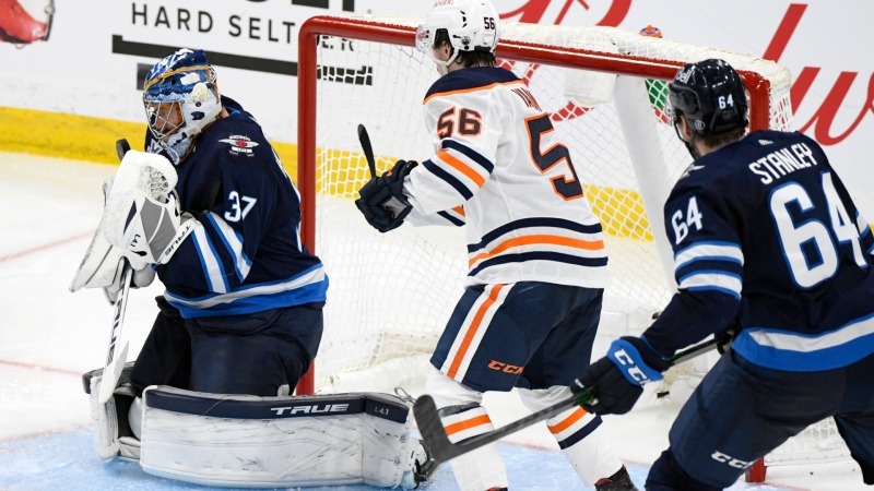 Winnipeg Jets goaltender Connor Hellebuyck (37) makes a save as Edmonton Oilers' Kailer Yamamoto (56) looks for the rebound during third period NHL Stanley Cup playoff action in Winnipeg on Monday, May 24, 2021. (THE CANADIAN PRESS/Fred Greenslade)