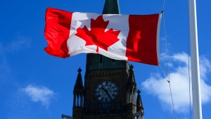 A Canada flag is pictured with the Peace Tower on Parliament Hill in Ottawa on Monday, April 12, 2021. THE CANADIAN PRESS/Sean Kilpatrick