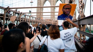 Demonstrators march across the Brooklyn Bridge from lower Manhattan to remember the murder of George Floyd on Tuesday, May 25, 2021, in New York. (AP / Eduardo Munoz Alvarez)
