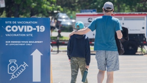 A man and boy walk into the Bill-Durnan COVID-19 vaccination site in Montreal, Monday, May 24, 2021, as the COVID-19 pandemic continues in Canada and around the world. THE CANADIAN PRESS/Graham Hughes