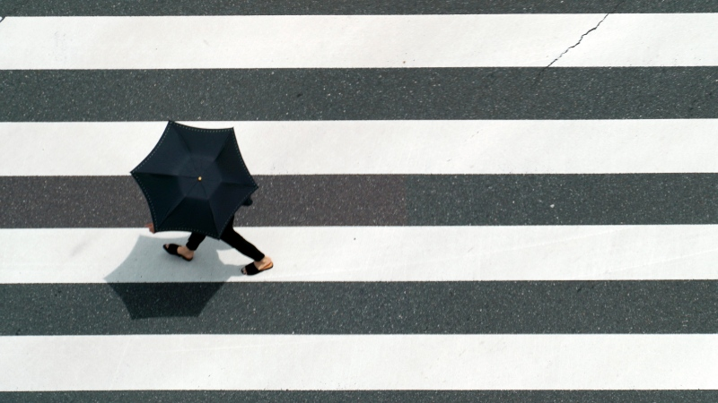 A person walks along a pedestrian crossing Wednesday, May 26, 2021, in Tokyo. (AP Photo/Eugene Hoshiko)
