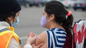 A person receives a COVID-19 vaccine at a drive-thru clinic at Richardson Stadium in Kingston, Ont., on Friday, May 28, 2021. THE CANADIAN PRESS/Lars Hagberg